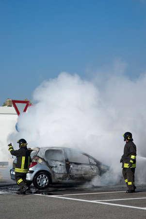 extinguishing: Firemen extinguishing a car fire