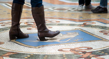 genitali: Milan, Italy - March 8, 2016: Mosaic floor of Vittorio Emanuele gallery in Milan. Tourist using the heel of his shoe to spinning on the genitals of the Bull for good luck. The tradition said that - if a person spins around three times with a heel on the t Editoriali