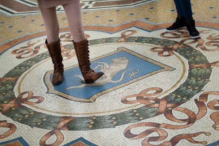 spins: Milan, Italy - March 8, 2016: Mosaic floor of Vittorio Emanuele gallery in Milan. Tourist using the heel of his shoe to spinning on the genitals of the Bull for good luck. The tradition said that - if a person spins around three times with a heel on the t Editorial