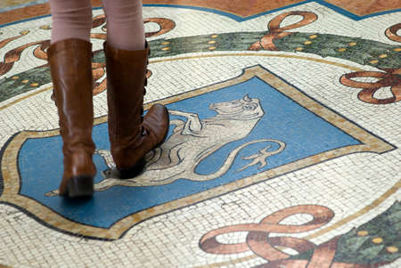 genitali: Milano, Italia - 8 Marzo, 2016: Mosaico pavimento della galleria Vittorio Emanuele a Milano. Turista con il tacco della scarpa per girare sui genitali del toro per buona fortuna. La tradizione dice che - se una persona gira intorno tre volte con un tacco sul t Editoriali