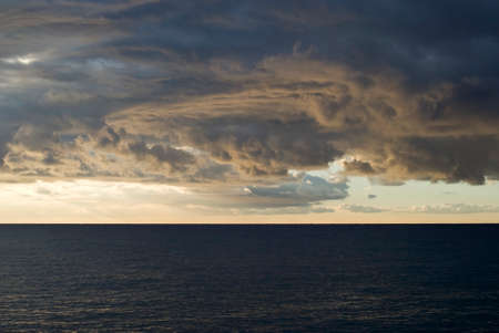 turbulent: Dark cumulus clouds hovering over the sea Stock Photo