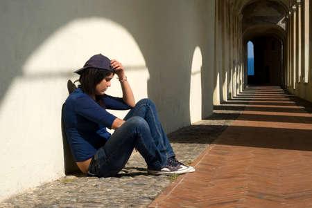 Droevig meisje zitten tegen een muur