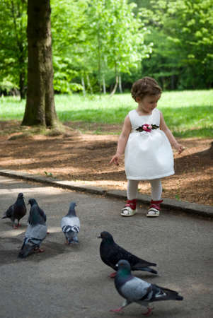 where to eat: Baby girl feeding pigeons Stock Photo