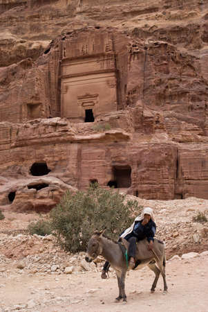 nabatean: Petra, Jordan - October 26, 2016: Beduin man riding donkey in the ancient Nabatean city of Petra, Jordan