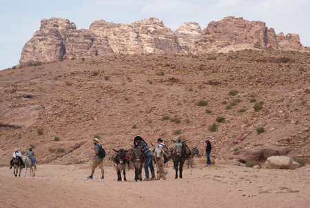 nabatean: Petra, Jordan - October 26, 2016: Beduin men riding donkeys in the ancient Nabatean city of Petra, Jordan