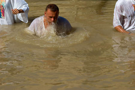 baptismal: Qasr el Yahud, Israel - October 29, 2016: A man immerses Themselves into the waters of the Jordan River baptismal site of Qasr el Yahud in Israel. The baptismal site on the banks of the Jordan River, is the site where according to Functional tradition, Je