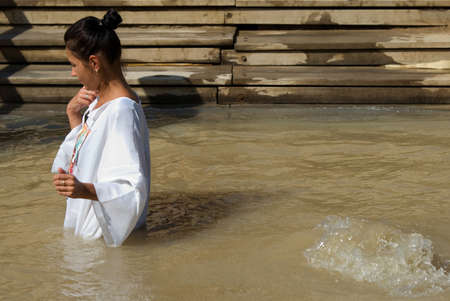 baptismal: Qasr el Yahud, Israel - October 29, 2016: A woman immerses Themselves into the waters of the Jordan River baptismal site of Qasr el Yahud in Israel. The baptismal site on the banks of the Jordan River, is the site where according to Functional tradition,  Editorial