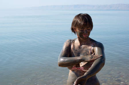 sourced: Woman applying natural mineral mud, sourced from the Dead Sea