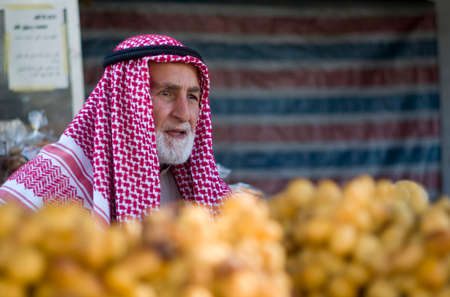 middle eastern clothing: Amman, Jordan - October 24, 2016: Jordanian senior man selling fruits in the downtown market of Amman Editorial