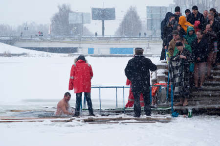 baptismal: Khmelnytskyi, Ukraine - January 19, 2012: People plunge in icy water in the Southern Bug River to celebrate the Epiphany religious holiday. Orthodox feast of Baptism is celebrated annually on 19 January. To Orthodox believers, water blessed by a priest on