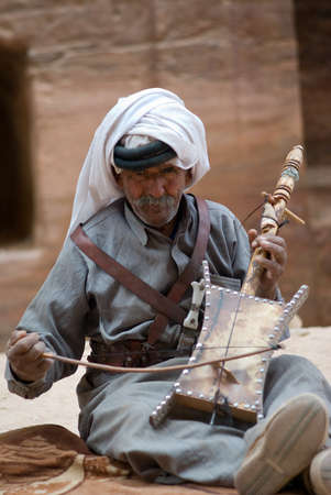 Petra, Jordan - October 26, 2016: Bedouin senior man playing stringed instrument at the ancient site of Petra in Jordan