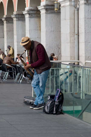african sax: Nice, France - March 21, 2016: An artist busker playing jazz saxophone on the Massena Square, Nice