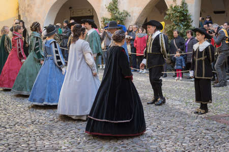 evoke: Taggia, Italy - February 26, 2017: Participants of medieval costume party in the historic city of Taggia in Liguria region of Italy. The actors acting out episodes of daily life in settings that evoke moments of life lived fully the seventeenth century. T