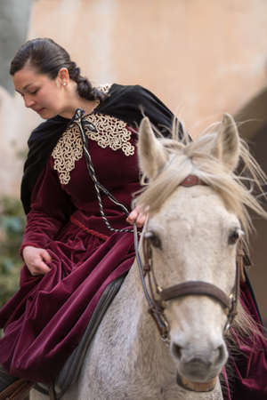 evoke: Taggia, Italy - February 26, 2017: Close-up of participant the medieval costume party in the historic city of Taggia in Liguria region of Italy. The actors acting out episodes of daily life in settings that evoke moments of life lived fully the seventeent
