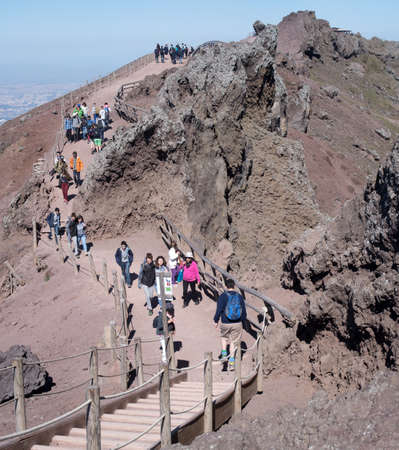 Naples, Italy - March 29, 2017: Tourists walk by the rim of the crater of Mount Vesuvius in Campania, Italy