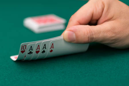 Poker player lifting the corners of cards Stock Photo