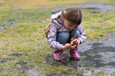 Het kind dat in een plas speelt Stockfoto