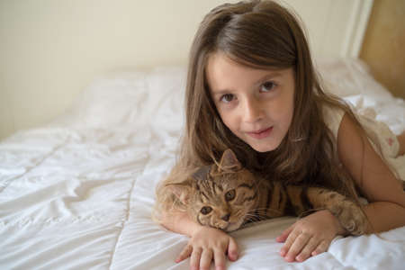 Young girl stroking cat lying on bed