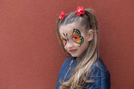Girl with butterfly painted on face posing on the wall background