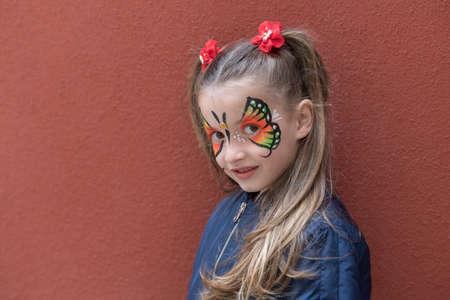 Mädchen mit Schmetterling gemalt auf Gesicht, das auf dem Wandhintergrund aufwirft Standard-Bild