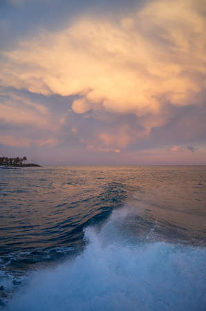 Dramatic colorful clouds at sunset hovering over the sea Stock Photo