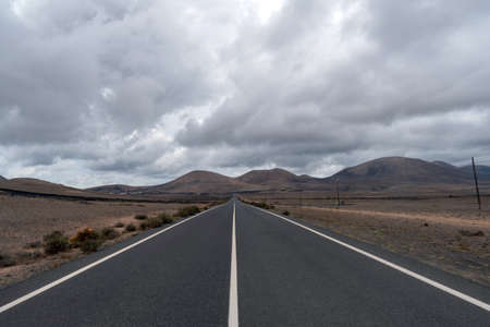 Long straight road in the Lanzarote Island, Canary Islands, Spain Banco de Imagens