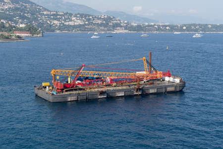 A construction crane barge begins land reclamation work off the coast of Monaco Imagens