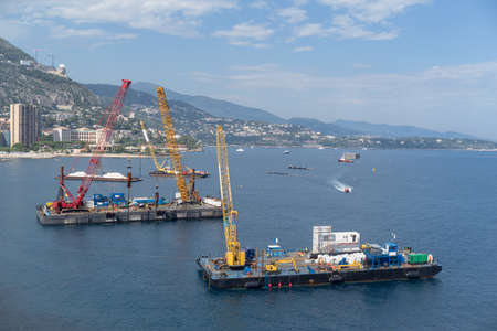 A construction crane barges begins land reclamation work off the coast of Monaco