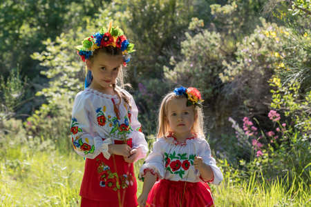 Sisters in traditional Ukrainian costumes playing in the spring countryside