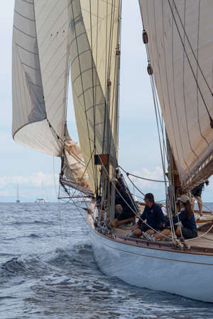 Imperia, Italy - September 7, 2019: Crew members aboard on sailboat Tuiga, flagship of the Monaco Yacht Club, during racing in Gulf of Imperia. Established in 1986, the Imperia Vintage Yacht Challenge Stage is a of the most important event in sailing the Editorial