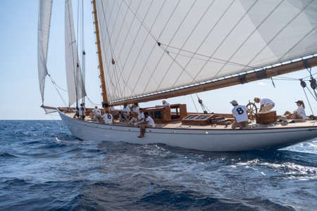 Imperia, Italy - September 7, 2019: Crew members aboard on Moonbeam IV classic sail yacht, during regatta in Gulf of Imperia. Established in 1986, the Imperia Vintage Yacht Challenge