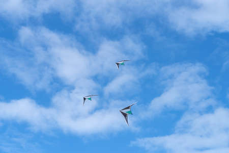Low angle view of kites flying in cloudy sky Reklamní fotografie