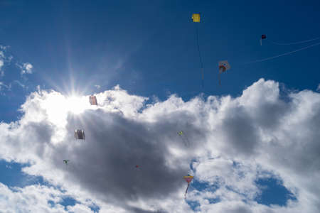 Kites are flying in the cloudy sky with the sun shining Reklamní fotografie