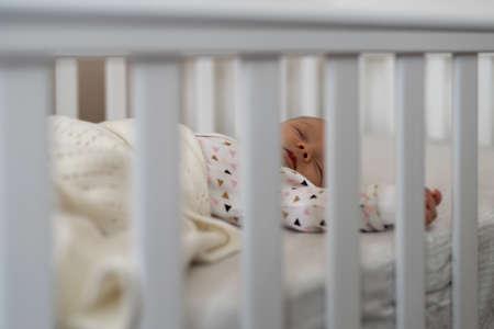 Lovely newborn baby girl sleeping in bed, view through crib bars Archivio Fotografico