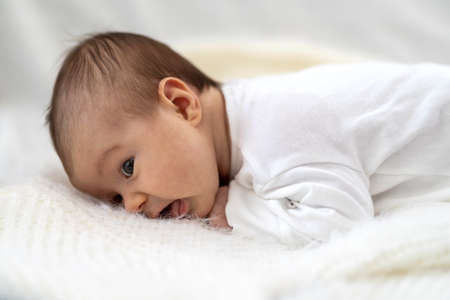 A 3 week old Caucasian baby girl smiles as he lays on a fluffy down duvet comforter on a bed