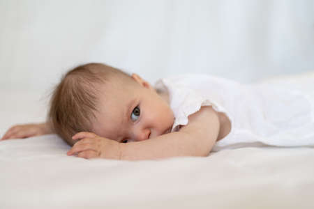 Caucasian baby girl as he lays on a fluffy down duvet comforter on a bed Фото со стока