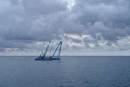 A construction crane barge floats beside the coastline during land reclamation work off the coast of Liguria, Italy