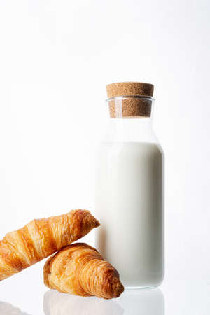Bottle with milk on a white background. Glass bottle. Natural cork. White drink. Cows milk. Two classic french croissants on a white background. Homemade baking.