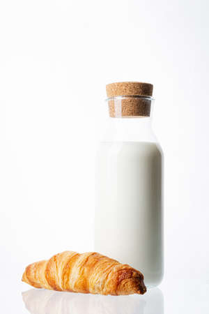 Bottle with milk on a white background. Glass bottle. Natural cork. White drink. Cows milk. One classic french croissant on a white background. Homemade baking. Фото со стока