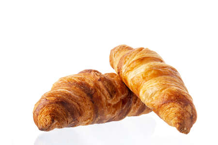 Two classic french croissants on a white background. Homemade baking.