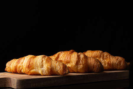 Three classic french croissants on a wooden board. Black background. Cutting board. Homemade baking.