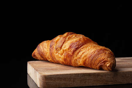 Classic french croissant on a wooden board. Black background. Cutting board. Homemade baking.
