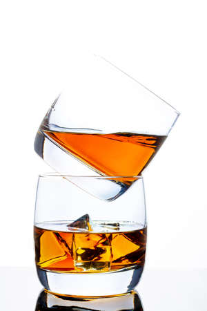 Two glasses of whiskey with ice. A pyramid of glasses. White background. Whiskey / Brandy / Cognac / Rum. Glass with a strong drink.