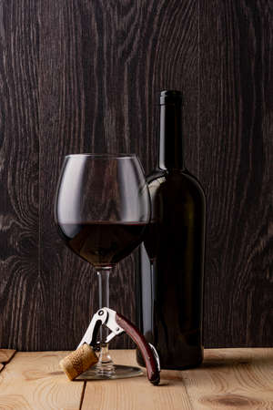 Wine bottle and a glass of wine. Wood background. Natural cork. Metal corkscrew.