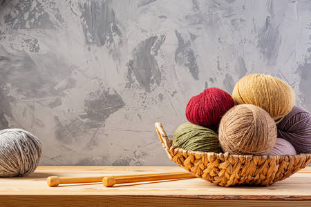 Skeins of yarn for knitting from natural wool in a wicker basket. Wooden surface or table. Background - concrete wall. Wooden knitting needles.