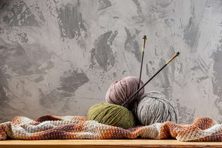 Skeins of yarn for knitting from natural wool on a wooden surface or table. Background - concrete wall. Wooden knitting needles.