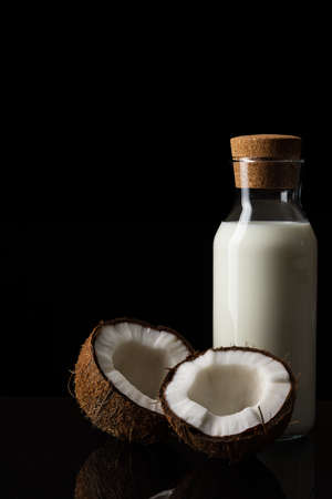 Coconut and a bottle of milk on a black background. Two halves of a nut. Coconut chopped in half. White flesh.
