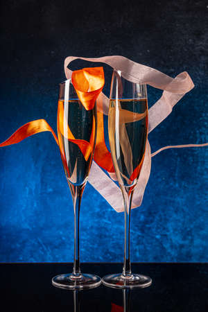 Two glasses with champagne on a black mirror surface. Flying satin ribbon. Blue background Concrete wall. Black glass. Crystal glass