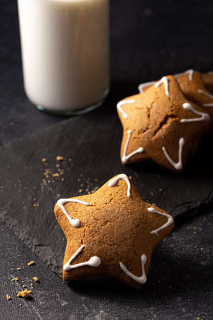 Handmade custard gingerbread in the shape of a star on a black background. Homemade baking. A bottle of milk in the background. Board made of stone. Baking crumbs.