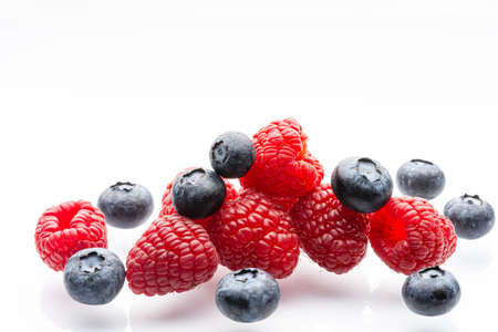Ripe wild berries on a white background. Garden raspberries. Ripe blueberries. White background. Red. Blue. Isolated.